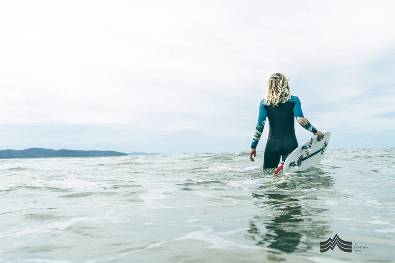 Brooke Mason entering the water in Tasmania with a surfboard