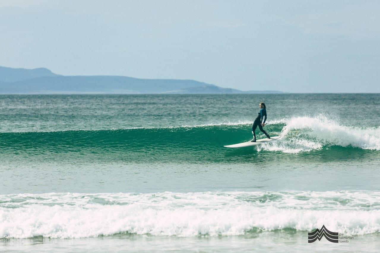Brooke Mason surfing on malibu surfboard in Tasmania