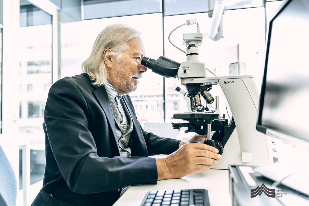 Professor Gustaaf Hallegraeff looking through a microscope