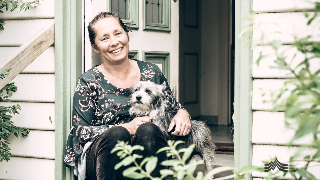 Ruth Langford sitting outside house with dog