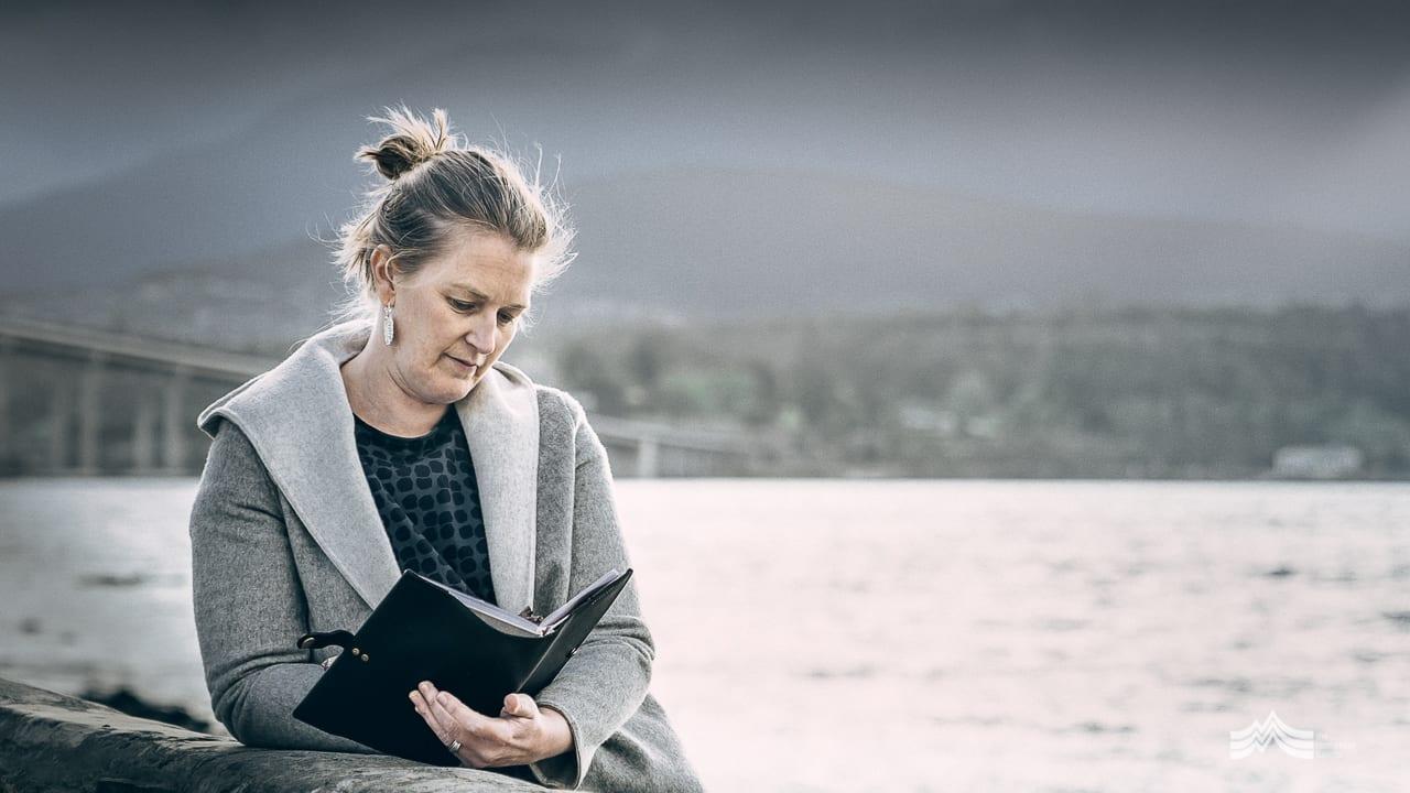 Amanda Mackinnon writing in her journal by the Derwent River Tasmania