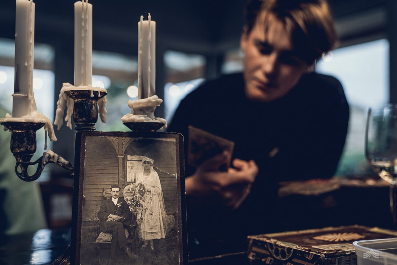 Gordon and Zella's wedding photograph leaning against an old candelabra. Young man looking on in background