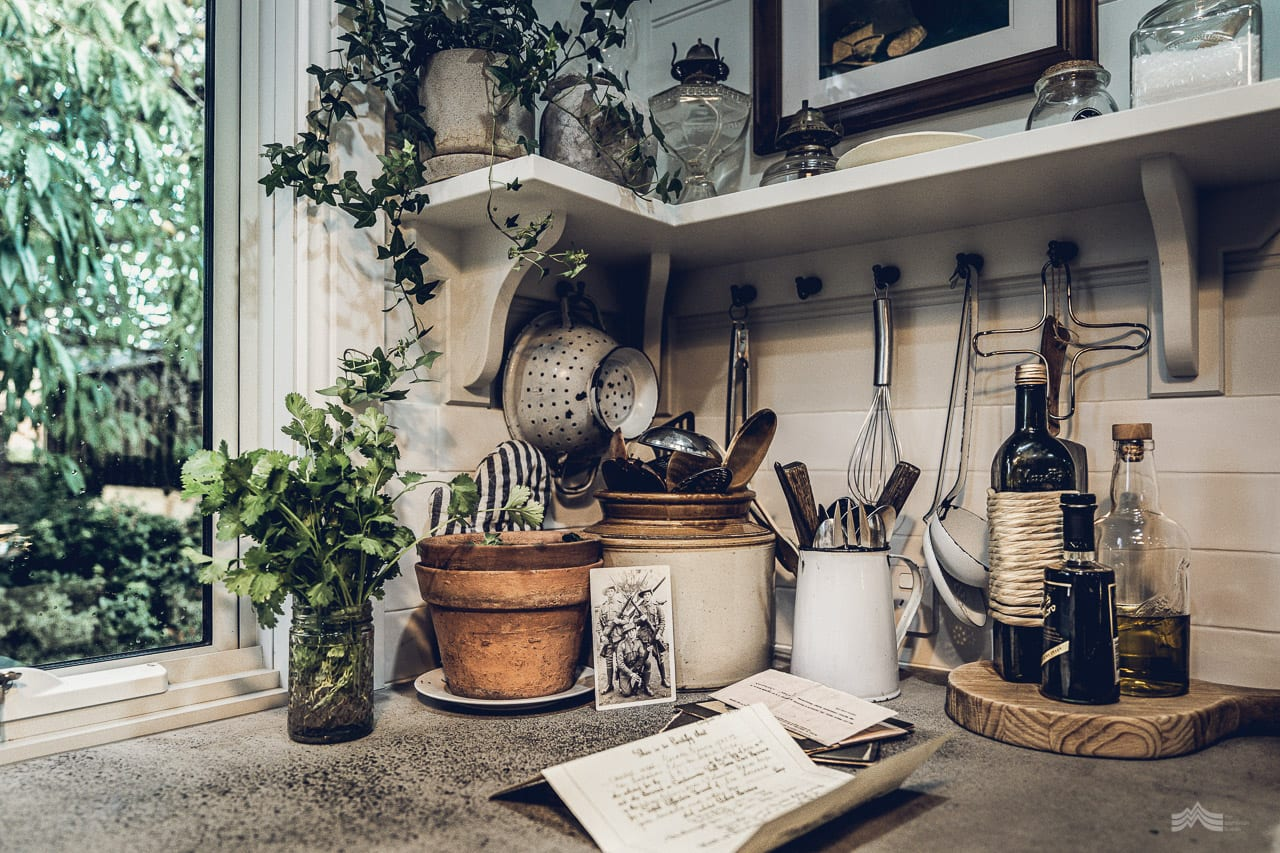 Corner of a country kitchen. An old war photograph propped up against a collection of old jars.