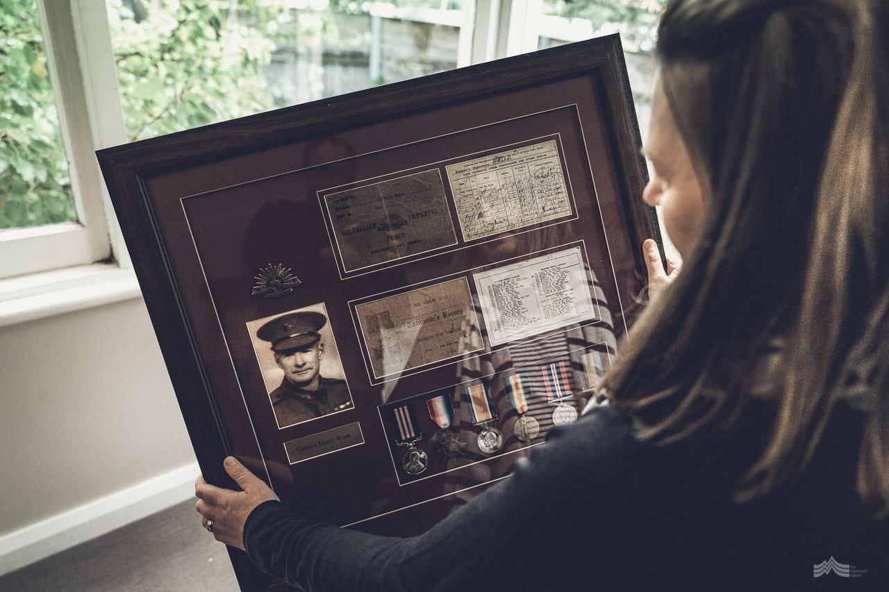 Woman holding Gordon's framed war medals and memorabilia